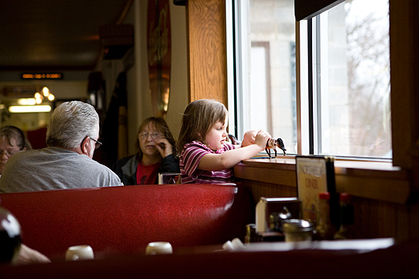 Girl playing with horse statues, Northside Diner, Chesterton IN